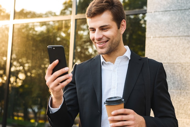 Portret wykonawczy biznesmen w garniturze trzymając telefon komórkowy, stojąc na zewnątrz w pobliżu budynku z kawą na wynos