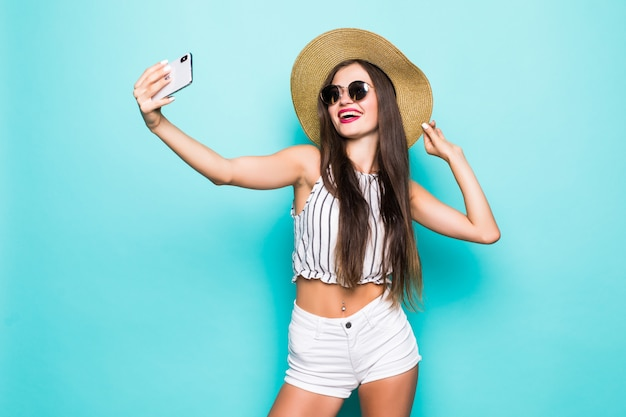 Portret wymarzonej dziewczyny sprawia, że blog selfie wysyła pocałunki do swoich obserwujących online na białym tle nad turkusowym turkusowym tłem
