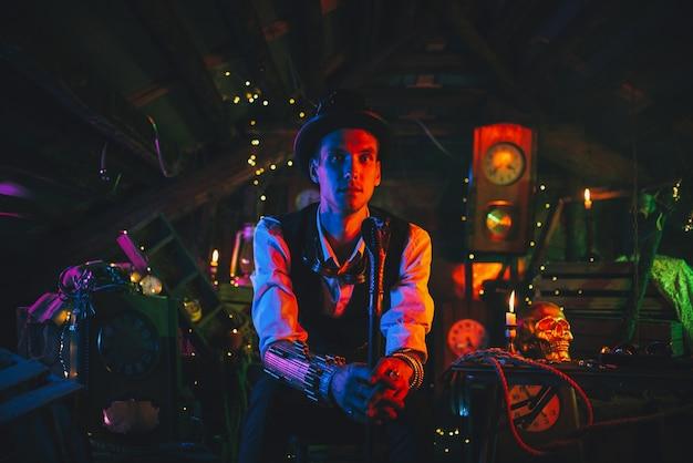 Portret wynalazcy mężczyzny w steampunkowym garniturze, cylindrze z laską w ręku siedzi w warsztacie zegarków z neonowym światłem. cyberpunkowy cosplay
