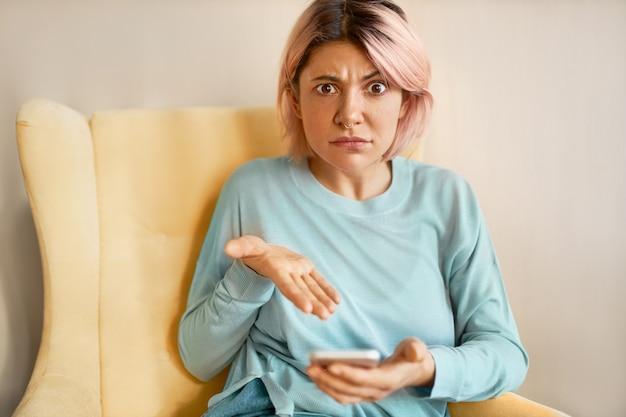 Portret wyrażający negatywne emocje zły i zirytowany młoda kobieta kaukaski, trzymając smartfon