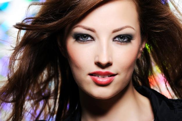 Portret wyrazistego wyglądu pięknej kobiety brunetka z zabawnymi włosami i jasnym makijażem