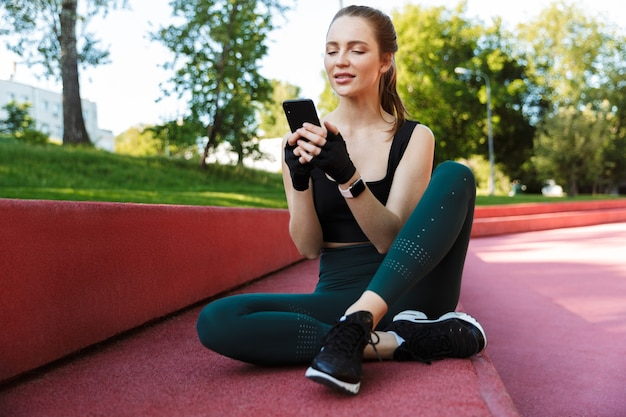 Portret wysportowanej młodej kobiety noszącej dres, trzymającej smartfona siedzącego na boisku sportowym podczas treningu w zielonym parku