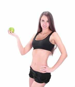 Portret wysportowanej młodej kobiety z zielonym jabłkiem. izolowany na białym tle
