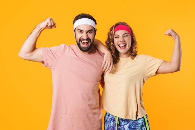Portret wysportowanej młodej pary noszącej opaski na głowę uśmiechniętej i pokazującej swoje umięśnione bicepsy izolowane nad żółtą ścianą