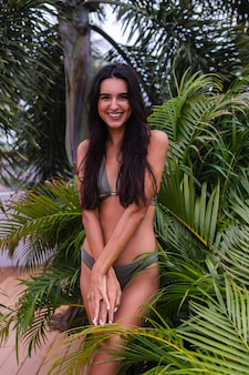 Portret wysportowanej, szczupłej kobiety w zielonym bikini z tropikalnymi liśćmi