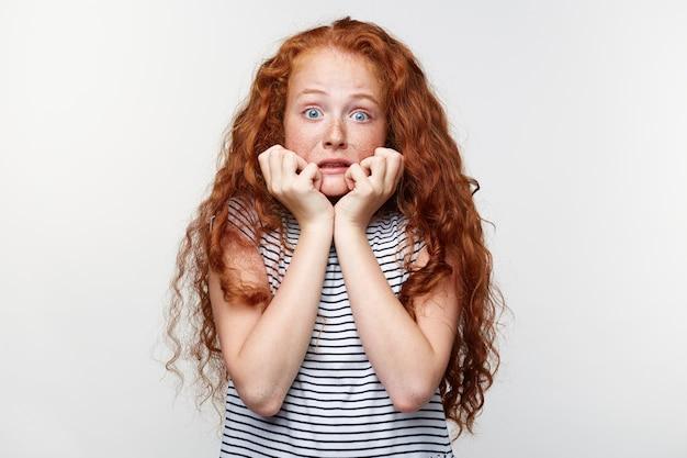 Portret wystraszonej dziewczynki z rudymi włosami i piegami, przestraszona i niespokojna obgryzająca paznokcie, patrząc na aparat z szeroko otwartymi oczami i odwracająca wzrok, odizolowana na białej ścianie.