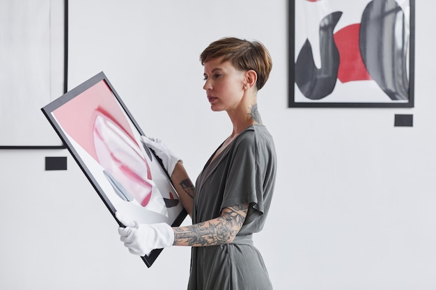 Portret wytatuowanej kreatywnej kobiety trzymającej obraz w talii podczas planowania wystawy w galerii sztuki,