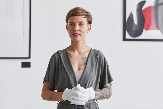 Portret wytatuowanej kreatywnej kobiety w pasie stojącej przed białą ścianą na wystawie galerii sztuki współczesnej,
