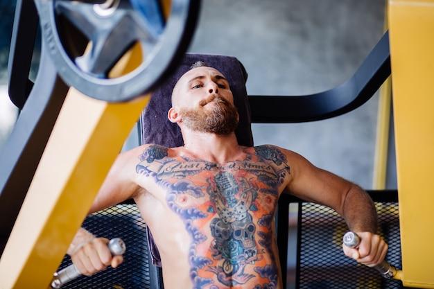 Portret wytatuowany brodaty mężczyzna ćwiczy na maszynie w siłowni w pobliżu okna