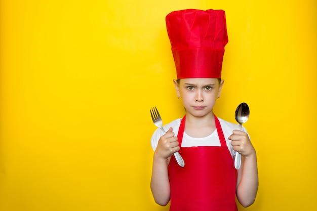 Portret wzburzona młoda dziewczyna w czerwonym szefa kuchni kostiumu trzyma łyżkę i rozwidla na kolorze żółtym