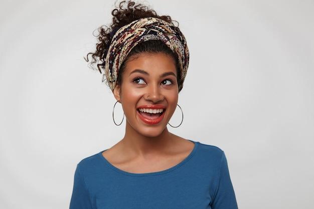 Portret wzburzonej młodej brunetki z zebranymi kręconymi włosami, patrzącej emocjonalnie w górę z szerokim uśmiechem, stojącej na białym tle w kolorowym stroju
