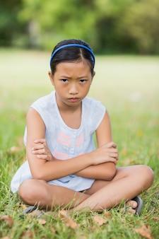 Portret wzburzony dziewczyny obsiadanie na trawie