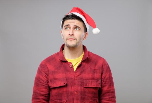 Portret wzburzony młody człowiek w czerwonym santa claus kapeluszu
