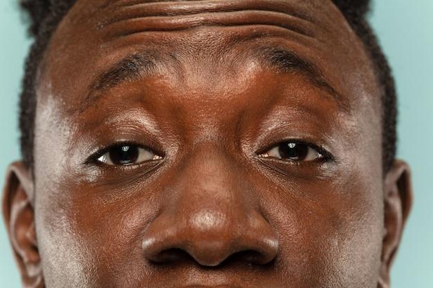 Portret z bliska afro-amerykańskiego młodego człowieka na niebieskim tle studio. piękny męski model o zadbanej skórze. pojęcie ludzkich emocji, wyraz twarzy, sprzedaż, reklama. oczy i policzki.