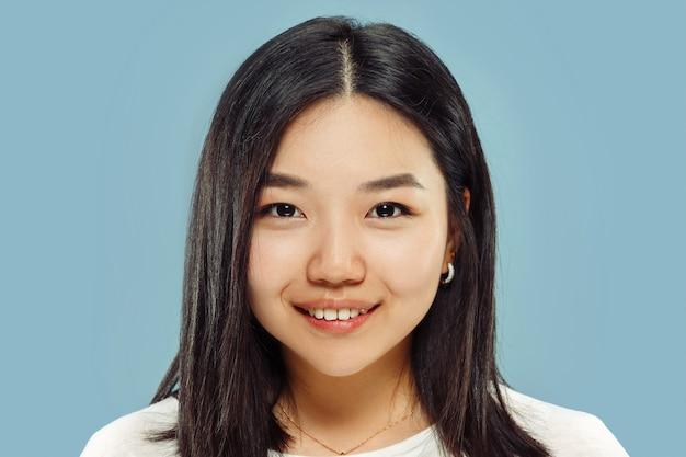 Portret z bliska koreański młodej kobiety. modelka w białej koszuli. uśmiechnięty i szczęśliwy. pojęcie ludzkich emocji, wyraz twarzy. przedni widok.