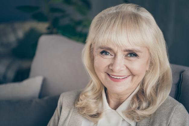 Portret z bliska ona ładna atrakcyjna urocza przyjazna miła wesoła, wesoła, siwowłosa blond babcia siedzi w domu ciesząc się czasem emerytury w mieszkaniu w domu mieszkanie w domu