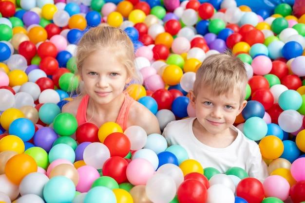 Portret z bliska uśmiechnięty blond mały chłopiec i dziewczynka leżący na wielokolorowych plastikowych kulkach w dużym suchym