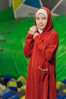 Portret z boku małej muzułmańskiej dziewczynki w hidżabie. koncepcja muzułmańskiej odzieży dla dzieci. na tle placu zabaw.