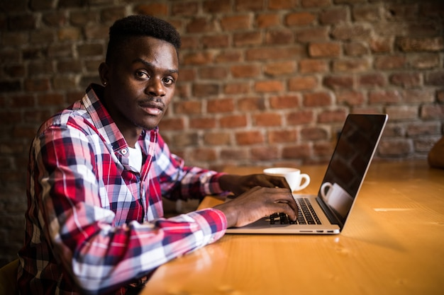 Portret z boku młodego mężczyzny afro american pracy laptopa w kawiarni