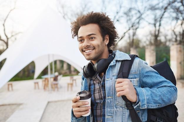 Portret z boku modnego szczęśliwego ciemnoskórego faceta trzymającego plecak i kawę podczas spaceru po mieście, uśmiechniętego i patrząc na bok, będąc w dobrym nastroju