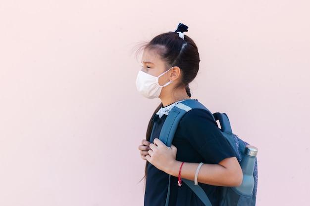 Portret z boku nastolatka z plecakiem i butelką termiczną wielokrotnego użytku po szkole. noszenie medycznej maski na twarz przeciwko koronawirusowi / covid-19.