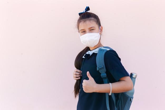 Portret z boku nastolatka z plecakiem i butelką termiczną wielokrotnego użytku po szkole pokazuje kciuki do góry.