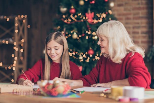 Portret z boku profilu babci wnuka, pisząc list do świętego mikołaja w urządzonym domu