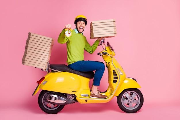 Portret z boku profilu faceta prowadzącego motorower przynoszący zegar stosu pizzy