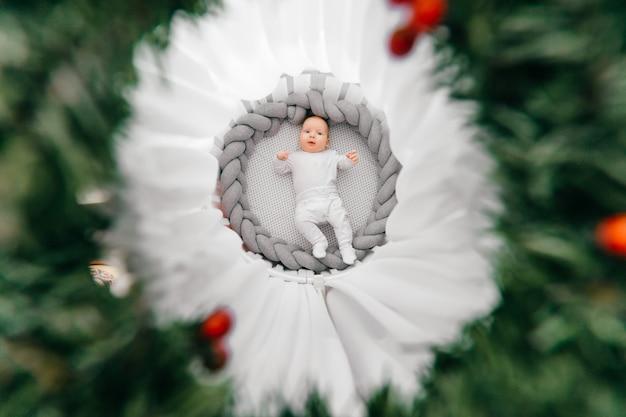 Portret z góry pięknego zabawnego nowonarodzonego chłopca leżącego na plecach w białym okrągłym łóżku z baldachimem. pokój dziecinny z dekoracyjnym wieńcem dla niemowlaka. urocze wesołe dziecko robiące miny rano.