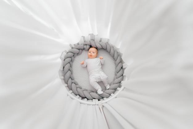 Portret z góry pięknego zabawnego nowonarodzonego chłopca leżącego na plecach w białym okrągłym łóżku z baldachimem.