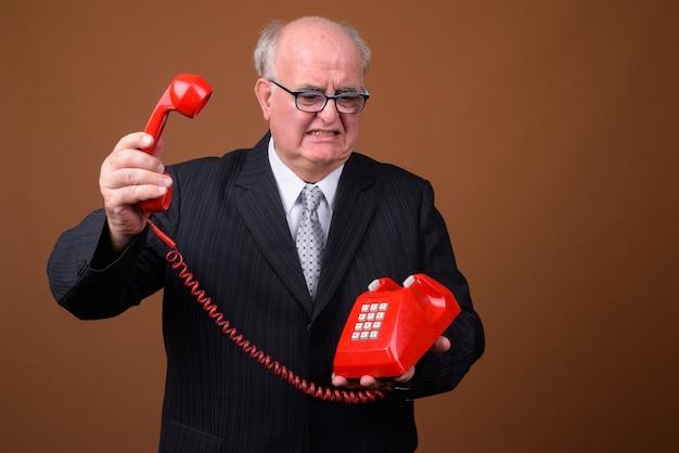 Portret z nadwagą starszy biznesmen rozmawia przez telefon