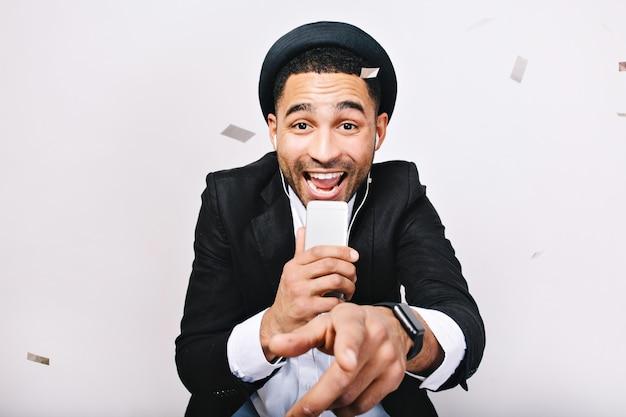 Portret z okazji imprezy karaoke podekscytowany przystojny facet w garniturze, kapelusz, zabawa. modny wygląd, wesoły nastrój, śpiew, muzyka, radość, wyrażanie pozytywności, radość.