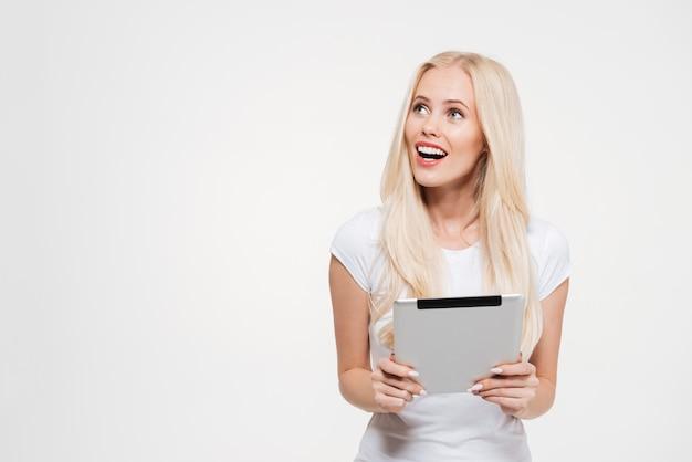 Portret z podnieceniem blondynki kobiety mienia pastylki komputer