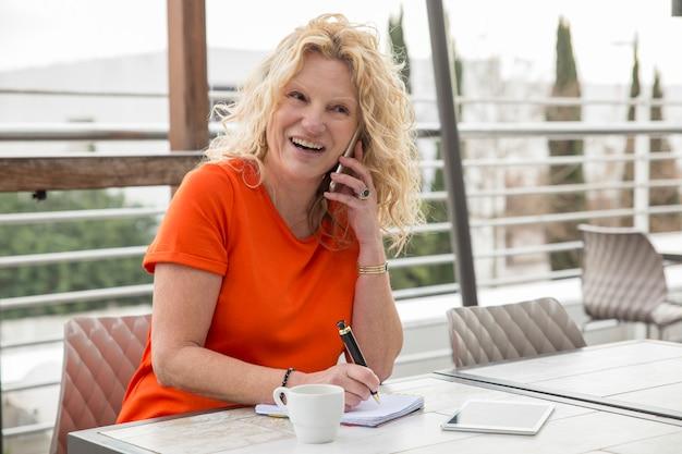 Portret z podnieceniem dojrzały bizneswoman opowiada na telefonie komórkowym