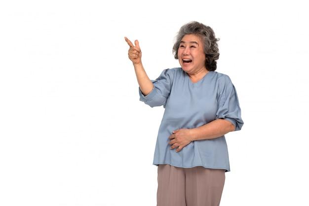 Portret z podnieceniem krzycząca azjatykcia starsza kobieta stoi palec wskazującego kopiować przestrzeń odizolowywającą nad biel ścianą i wskazuje, no! no i zaskakujący pojęcie