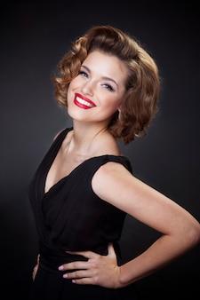 Portret z przodu eleganckiej, uśmiechniętej młodej kobiety, modelki z czarującą fryzurą i makijażem
