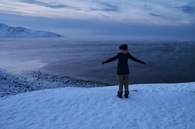 Portret z tyłu ciepło ubranej kobiety w rozmyciu stojącej przed morzem, patrząc daleko, patrząc na zimową szorstką wodę w zwolnionym tempie