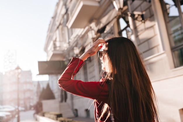 Portret z tyłu długowłosej dziewczyny spacerującej po mieście w słoneczny dzień