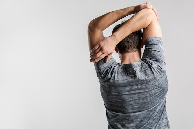 Portret z tyłu młodego wysportowanego mężczyzny w sportowej robi ćwiczenia podczas ćwiczeń na białym tle