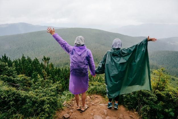 Portret z tyłu podróżującej pary w płaszczach przeciwdeszczowych stoi na szczycie góry z rozłożonymi rękami