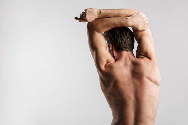Portret z tyłu półnagi atletyczny mężczyzna robi ćwiczenia podczas ćwiczeń na białym tle