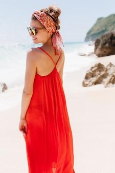 Portret z tyłu radosna kaukaska modelka nosi wstążkę stojącą na naturze. plenerowe zdjęcie ekstatycznej opalonej dziewczyny w długiej letniej sukience z delikatnym uśmiechem na plaży.