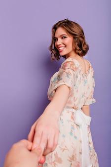 Portret z tyłu śmiejąc się romantycznej dziewczyny trzymającej rękę fotografa