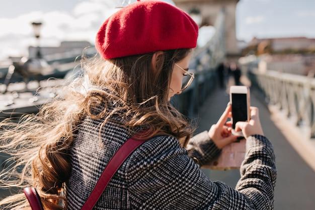 Portret z tyłu stylowa kobieta w tweedowej kurtce trzymając telefon i robiąc zdjęcie krajobrazu miasta