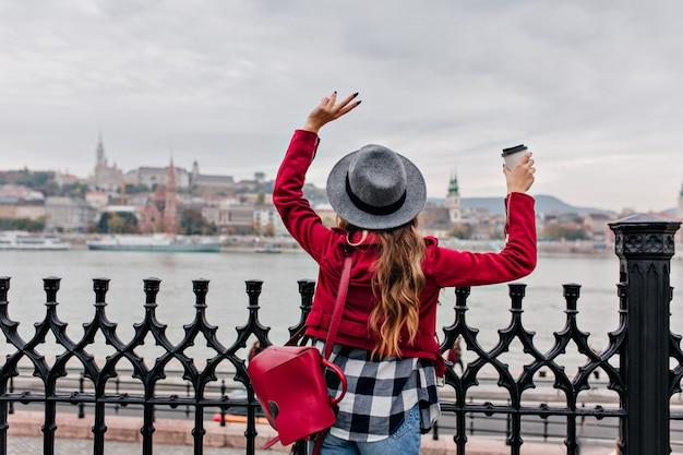 Portret z tyłu stylowa młoda kobieta w kraciastej koszuli, machając rękami na miasto