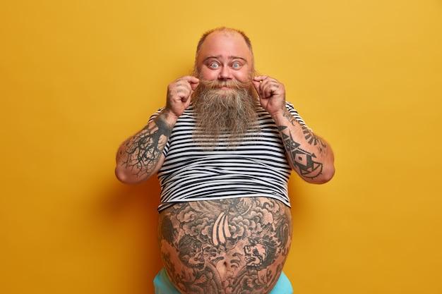 Portret zabawnego brodatego mężczyzny zwija wąsy, ma wytatuowane ramiona i brzuch, ubrany w niewymiarową koszulkę bez rękawów w paski, ma problem z otyłością i nadwagą, odizolowany na żółtej ścianie