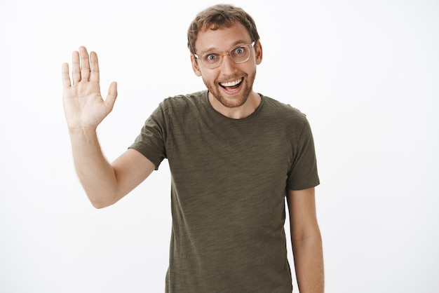 Portret zabawnego, entuzjastycznego, zarośniętego rasy kaukaskiej faceta w ciemnozielonej koszulce i przezroczystych okularach podnoszącego dłoń i witającego się