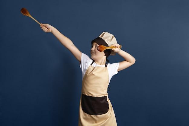 Portret zabawnego europejskiego małego chłopca szefa kuchni w czapce i fartuchu tańczącym na tle pustej ściany studia, trzymając w rękach drewniane łyżki, bawiąc się podczas gotowania sosu pomidorowego do makaronu
