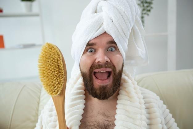 Portret zabawnego faceta nosić turban ręcznik trzymający w dłoniach pędzel do masażu, gdy siedzi na kanapie męskiej skóry