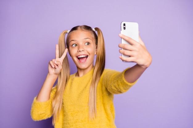 Portret zabawnego, funky dziecka warkocze kucyki ciesz się podróżą weź selfie, spraw, by znaki v nosiły stylowy żółty sweter odizolowany na fioletowej ścianie